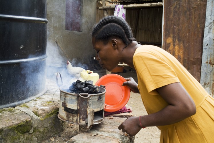 Yael Keki prepares a meal outside of the home of her brother where she and her family live Nabugoye Hill.