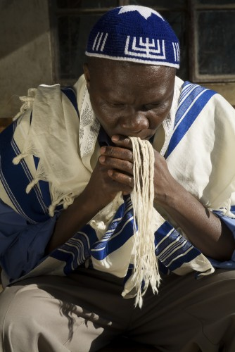 Rabbi Aaron Kintu Moses praying outside his home on the 4th day of mourning after the death of his six month old baby boy. Nangola village