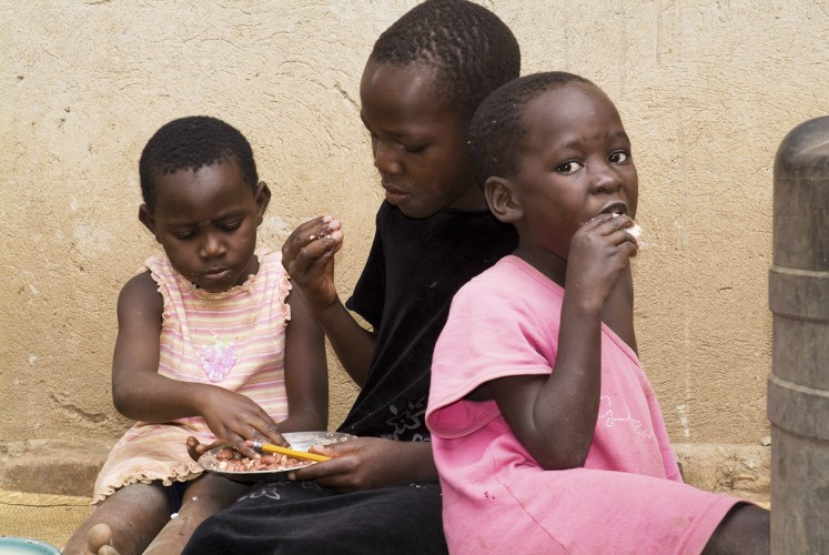 Children eating  a meal of beans and matoke at JJ Keki's home in Nangola village