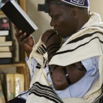 Rabbi Aaron Kintu Moses kisses the fringes of his prayer shawl whilst saying the Shama. A custom done, whilst reciting parts of the Shama.  This prayer is one of the major prayers in Judaism. It contains 3 paragraphs: Deut. 6, 4-9: 11,13-31 and Numb.15,37-41. Morning service, Moses Synagogue, Nabugoye Hill.